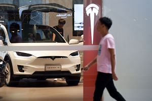 File photo showing a man visiting a Tesla showroom in Beijing. Most US businesses operating in China oppose using tariffs as a weapon to solve their problems.