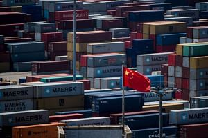 File photo of a Chinese flag in front of containers at the Yangshan Deep-Water Port, an automated cargo wharf, in Shanghai.