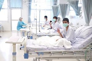 Boys rescued from a flooded cave in Thailand wearing mask and resting in a hospital in Chiang Rai, on July 11, 2018.