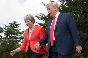 US President Donald Trump (right) and Britain's Prime Minister Theresa May held hands and praised each other's leadership, on July 13, 2018.