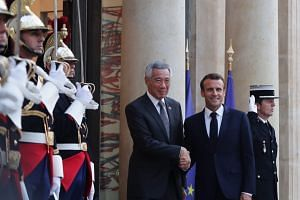 French President Emmanuel Macron welcoming Singapore Prime Minister Lee Hsien Loong at the Eylsee Palace.