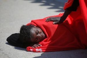 A migrant at the port of Tarifa in southern Spain last Saturday, after she was rescued from a toy dinghy in the Strait of Gibraltar. Germany said yesterday that it would take in 50 migrants, matching similar pledges by France and Malta. Italy has sin