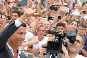 Cristiano Ronaldo greeting fans as he arrives for his medical at Juventus' medical centre in Turin on July 16, 2018.