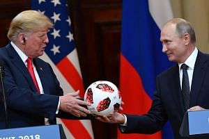 Russia's President Vladimir Putin (right) offers a ball of the 2018 football World Cup to US President Donald Trump during a joint press conference after a meeting at the Presidential Palace in Helsinki, on July 16, 2018.