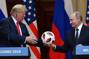 Russia's President Vladimir Putin (right) offers a ball of the 2018 World Cup to US President Donald Trump during a joint press conference after a meeting at the Presidential Palace in Helsinki, on July 16, 2018.