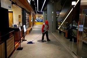File photo showing a cleaner mopping the floor at the Lotte World Mall in Seoul.