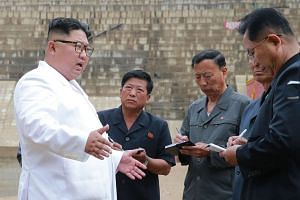 North Korean leader Kim Jong Un (left) inspecting the construction site of an electrical power plant at the Orang river in the North Hamgyong Province of North Korea.