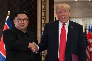 Kim and Trump shake hands following a signing ceremony at their historic summit in Singapore.