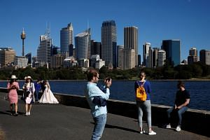 People seen against the skyline of Sydney, Australia, on May 7, 2018. Australia's location makes it a better base for doing business in emerging Asian economies.