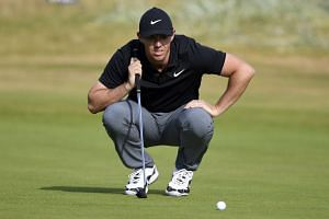 Rory McIlroy of Northern Ireland lines up a putt on the first day of the British Open.