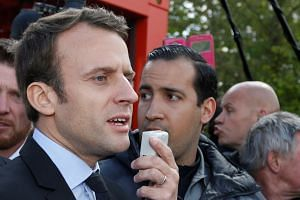 Macron (left) is flanked in an April 2018 photo by Alexandre Benalla (centre).
