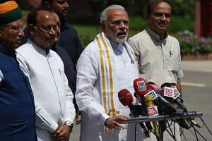 Indian Prime Minister Narendra Modi (second from right), accompanied by senior Bharatiya Janata Party leaders, addresses media representatives after arriving for the monsoon session of Parliament in New Delhi, on July 18, 2018.