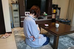 """Ms Sayako, who declined to give her full name, holding her baby during an interview in Tokyo. She had been trying to conceive a second child when her boss at a daycare centre told her to stop, saying she had missed her """"turn"""", as prescribed on a """"pre"""