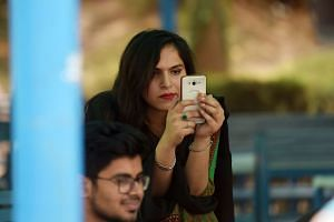 A student using her mobile phone at a campus in Islamabad. Many of the 46 million people below the age of 35 who are registered to vote in the upcoming nationwide elections are savvy social media users who are using platforms like YouTube and Faceboo