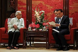 Chinese Premier Li Keqiang reads a letter from Malaysia's Prime Minister Mahathir Mohamad as Kuala Lumpur's special envoy Daim Zainuddin looks on at the Zhongnanhai Leadership Compound in Beijing last Wednesday. Mr Daim was in China to try and get ti