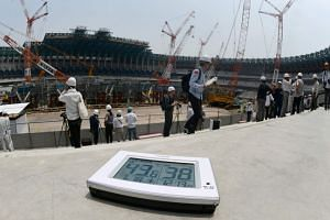 A digital thermometer showing the temperature going past 40 deg C, at the construction site for the new National Stadium in Tokyo on July 18, 2018.