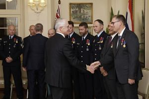 Dr Richard Harris shakes hands with Australian Prime Minister Malcolm Turnbull as he stands with other members of the Thai cave rescue team during a ceremony at Government House in Canberra on July 24, 2018.