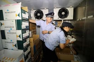 Law enforcement personnel check the vaccine supply in Rongan, China, on 23 July 2018, after Chinese Premier Li Keqiang ordered new investigations into a DPT vaccine scandal.