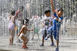 Children play in the water jets at a park near Nerima in Tokyo as temperature rose up to 39.6 degrees C in Japan's latest heatwave that has killed 65 people and is now being classified as a natural disaster.