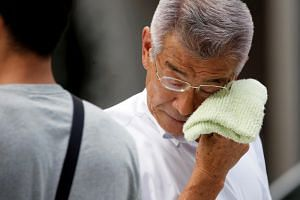 A Japanese businessman wiping his face while walking on a street during a heatwave that has resulted in the hospitalisation of 22,647 people.