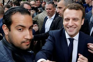 Benalla (left) in a press photo with Macron (right) at a campaign event in Rodez, France, in May 2017.