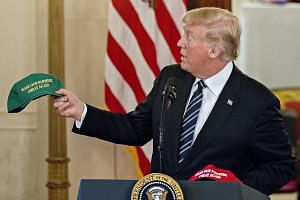 "President Donald Trump with a ""Make Our Farmers Great Again"" cap while speaking at a Made in America products showcase in the Cross Hall of the White House on Monday."