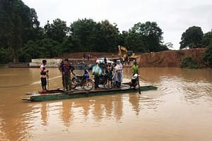 People use a makeshift ferry to cross the swollen Xe Khong river due to flash flooding in Sanamxai, Attapeu province, on July 25, 2018.