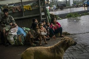 A family displaced by a dam failure and flooding waits outside an empty coffee warehouse in Paksong, Laos.
