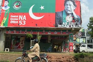 A Pakistani motorcyclist rides past a billboard featuring an image of Pakistan's cricketer-turned-politician Imran Khan, in Islamabad, on July 26, 2018.
