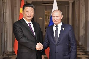 Chinese President Xi Jinping (left) called for the United Nations and the World Trade Organisation to fight unilateralism and protectionism while Russian President Vladimir Putin encouraged closer ties and stronger trade among the Brics members.