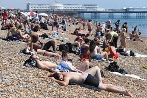 People enjoy the warm weather on Brighton beach in Britain on July 26, 2018.