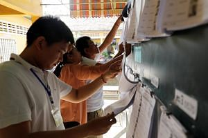 Election officials examining voter lists at polling station located at a school in Phnom Penh, on July 28, 2018. Officials expect more than 60 per cent of the whole country to vote in Cambodia's upcoming election.