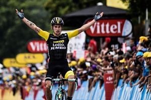 Slovenia's Primoz Roglic celebrates as he crosses the finish line to win the 19th stage.