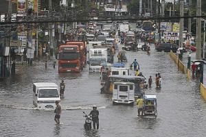 Motorists and pedestrians moving through a flooded road on July 18 in Marilao town in Bulacan Province, north of Manila. The Philippines and Indonesia are the most vulnerable to extreme weather, while Thailand and Singapore are less at risk, accordin