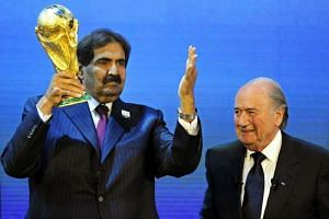 A file photo taken on Dec 2, 2010, shows then Fifa president Joseph Blatter and then Qatar Emir Sheikh Hamad bin Khalifa Al-Thani with the World Cup trophy after Qatar was announced to host the 2022 World Cup in Zurich.