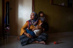 Siti Noor Azila with her two daughters in her family's home. Her husband, a 41-year-old man, had just married an 11-year-old girl, causing her and his first wife to band together.