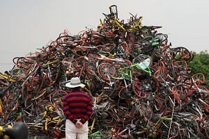 Bicycles from various bike-sharing firms lying in a tangled heap in Shanghai last month. China's