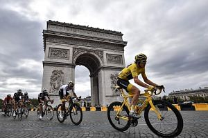 Geraint Thomas, wearing the leader's yellow jersey, riding past the Arc de Triomphe on the last stage of the Tour de France on Sunday. The 32-year-old, dogged by bad luck on several previous Tours, won the classic race on his ninth attempt.