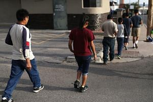 A man and his daughter walk with other parents and children to play soccer as they are cared for in an Annunciation House facility after they were reunited on July 24, 2018 in El Paso, Texas.