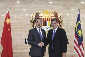 China's Foreign Minister Wang Yi (left) and Malaysian Foreign Affairs Minister Saifuddin Abdullah shake hands during Mr Wang's working visit in Putrajaya, Malaysia, on July 31, 2018.