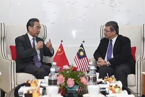 Visiting Chinese Foreign Minister Wang Yi (left) meeting his Malaysian counterpart Saifuddin Abdullah in Putrajaya yesterday. Mr Wang said China attaches high importance to its relations with Malaysia.