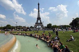 People cooling themselves at the Fontaine du Trocadero in front of The Eiffel Tower in Paris.