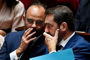 Prime Minister Edouard Philippe (left) chats with Minister of State for Relations with Parliament Christophe Castaner during the debate.