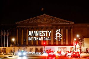 The logo of NGO Amnesty International projected onto the Palais Bourbon, the seat of the French national assembly, on June 18, 2018.