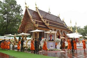The rescued Thai boys ordained as novice Buddhist monks walk in procession by the portrait of former Thai Navy SEAL diver Saman Gunan (centre) at the Wat Phra That Doi Tung temple on July 25, 2018.