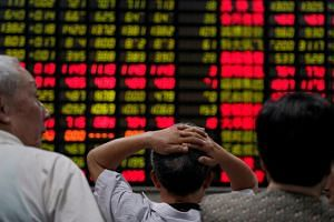 investors look at an electronic board showing stock information at a brokerage house in Shanghai on June 20, 2018.