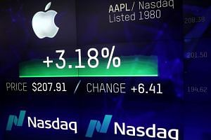 An electronic screen displays the Apple stock price at the Nasdaq Market Site in New York City.