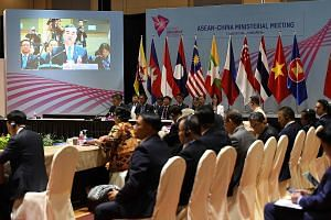 China's Foreign Minister Wang Yi (on screen) delivering his opening statement during the Asean-China Ministerial Meeting in Singapore yesterday. The first phase of the Asean-China maritime exercise will involve table-top discussions and a scenario-ba