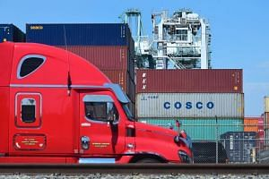 A container delivery truck passes containers stacked at the Port of Long Beach in Long Beach, California including one from Cosco, the Chinese state-owned shipping and logistics company.