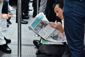 A commuter on an MRT train reading The Straits Times, which was launched in 1845.
